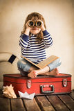 Adventure. Funny kid playing with toy sailing boat indoors. Travel and adventure concept Stock Photos