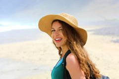 Adventure girl with backpack and straw hat looking to the camera. Young woman exploring Canarian Coast. With sand dunes of Lanzarote, Spain Royalty Free Stock Image