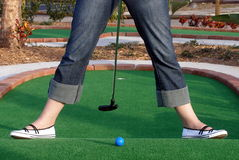 Adventure Golf. Playing Adventure Golf, downhill shot, ball, club and hole Stock Image