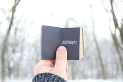 Adventure, hand holding a book with text on background of snowy winter park Royalty Free Stock Photos