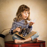 Adventure. Happy kid playing with toy sailing boat indoors. Travel and adventure concept Stock Images