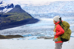 Adventure hiking woman by glacier on Iceland. Hiker trekking walking by glacial lagoon / lake of Fjallsarlon, Vatna glacier, Vatnajokull National Park. Young Stock Photo