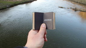 Adventure idea, traveler holds a book with text. The traveler holds a book with the inscription on the background of the river stock video footage