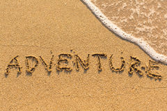 Adventure - inscription by hand on beach sand Stock Photography