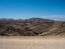 Adventure journey scene on dirt road trip through layers of great rock mountain texture panorama landscape view background. And clear blue sky, Namibia Royalty Free Stock Photos
