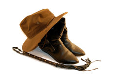 Adventure kit. Brown hat with black leather boots and a whip for an adventure kit Dark heavy hat with wide brim Whip of many tails made of leather and brads royalty free stock photo