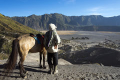 Adventure of a man with horse overlooking Hindu temple called Pura Luhur Poten Stock Image