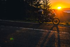 Adventure motorcycle, silhouette touristic motorbike. the mountain peaks in the dark colors of the sunset. Copy space. Copy space royalty free stock photography