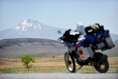 Adventure motorcycle travel in Turkey. Adventure motorcycle loaded with luggage and Turkey's Mount Erciyes on the background Royalty Free Stock Image
