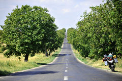 Adventure Motorcycling. The open and empty road and a motorcycle ready for adventure Royalty Free Stock Photography