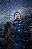 Adventure mountain man. In snow expedition with climbing gear and determination Royalty Free Stock Image