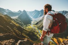Adventure in mountains Man with red backpack alone on cliff. Travel lifestyle concept active summer vacations aerial view landscape stock photography
