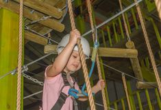 The girl in the white helmet in the adventure Park. In the adventure Park the kid in the white helmet Stock Photography