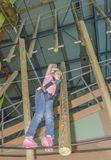 Overcomes obstacles girl in a white helmet at the adventure Park Stock Images