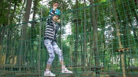 Adventure park and little girl. Rope suspension bridge extreme sport entertainment leisure activity physical exercise forest trees child caucasian white stock footage