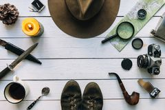 Adventure planning flat lay. Travel vintage gear on white wooden table. Including film camera, hat, knife, magnifier, compass. Exploring poster, postcard stock photos