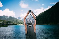 Adventure seeker man makes photo of lake Stock Photography
