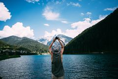 Adventure seeker man makes photo of lake Royalty Free Stock Photography