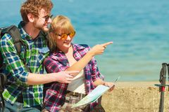Couple backpacker with map by seaside. Adventure, summer, tourism active lifestyle. Young couple backpacker looking at map by seaside, plan their sightseeing Royalty Free Stock Photography