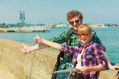 Couple backpacker with map by seaside hitchhiking. Adventure, summer, tourism. Young couple backpacker hitchhiker with map by seaside hitchhiking with thumb up Royalty Free Stock Photo