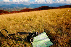 Adventure theme. An image of binoculars and map on dry grass. Adventure theme Royalty Free Stock Photos