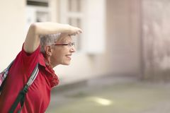 Adventure time for an older lady. Happy senior woman looking ahead with her hand at her forehead, excited to leave home and go on a trip Royalty Free Stock Image