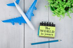 plane and note pad with text & x22;The world is yours& x22; on white wooden table Stock Photos