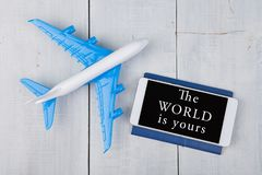 plane, passport and smartphone with text & x22;The world is yours& x22; on white wooden table Royalty Free Stock Image