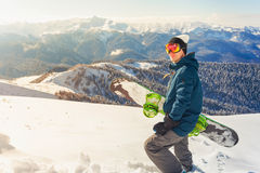 Adventure to winter sport. Snowboarder man hiking at mountain Stock Photography