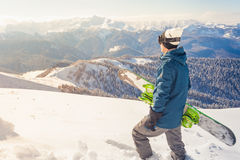 Adventure to winter sport. Snowboarder man hiking at mountain Stock Photos