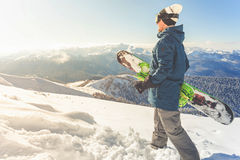 Adventure to winter sport. Snowboarder man hiking at mountain Royalty Free Stock Photos