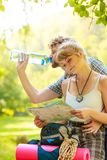 Couple hikers resting in forest drinking water Royalty Free Stock Photography