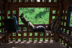 Adventure, tourism, enjoying summer time - young tourist man hiker with backpack sticks resting on bench in forest trail Royalty Free Stock Photo