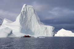 Adventure tourists - Scoresbysund - Greenland. Adventure tourists near a huge Iceberg in Scoresbysund in eastern Greenland Stock Images