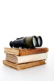 Adventure and travel books. Antique books and binoculars symbolizing adventure and travel book, on a white background Royalty Free Stock Photo
