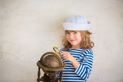Adventure and travel concept. Happy child playing with vintage nautical things. Kid having fun at home. Summer sea dream and imagination. Adventure and travel Stock Photo