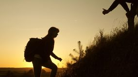 Adventure and travel concept. Traveler man holds out a woman's hand to a traveler climbing to top of the hill. Tourists. Adventure and travel concept. Traveler stock footage