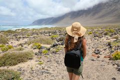 Adventure travel concept. Young woman looking to impressive fantastic landscape of Lanzarote. Royalty Free Stock Image