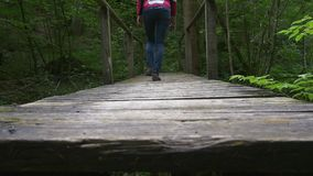 Adventure travel. Hiking across the bridge. Legs of hiker woman walk across a wooden bridge on a hiking trail in forest, slow motion stock video