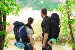 Adventure, travel, tourism, hike and people concept. Smiling couple with backpacks outdoors stock photo