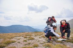 Adventure, travel, tourism, hike and people concept - group of smiling friends with backpacks and map outdoors.  stock photography