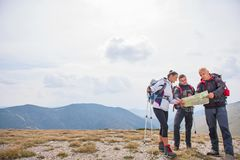 Adventure, travel, tourism, hike and people concept - group of smiling friends with backpacks and map outdoors.  royalty free stock image