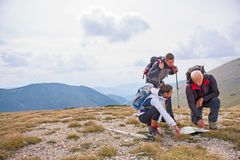 Adventure, travel, tourism, hike and people concept - group of smiling friends with backpacks and map outdoors.  royalty free stock images