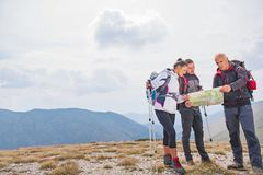 Adventure, travel, tourism, hike and people concept - group of smiling friends with backpacks and map outdoors.  stock photo