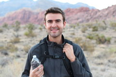 Adventure, travel, tourism, hike and people concept - man holding water bottle and black backpack hiking in the desert. Rocky mountains stock photos