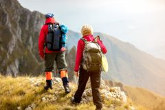 Adventure, travel, tourism, hike and people concept - smiling couple walking with backpacks outdoors.  Royalty Free Stock Photos