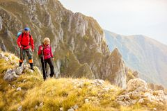 Adventure, travel, tourism, hike and people concept - smiling couple walking with backpacks outdoors.  stock photography