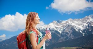 Smiling woman with backpack over alps mountains Royalty Free Stock Image