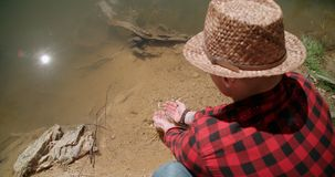 Young man dipping hands into lake. Stock Images