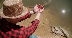 Young man dipping hands into lake. Stock Photo